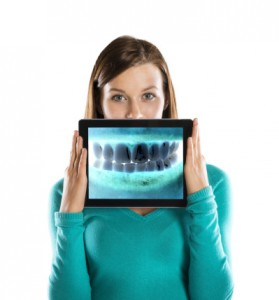 Woman holding digital image in front of her mouth from the Dentist 29464 trusts