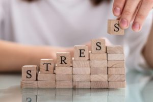 "person holding blocks with letters of the word ""stress"""