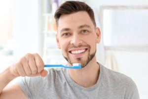 Man in grey shirt brushing his teeth for a healthy mouth